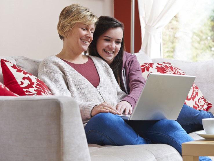 Mutter und Tochter planen Landausflüge auf dem Sofa mit Laptop.