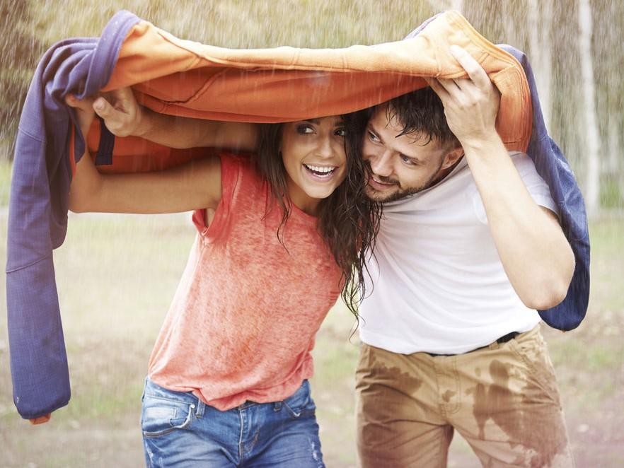 Junges Paar wird auf Landausflug von Regen überrascht.